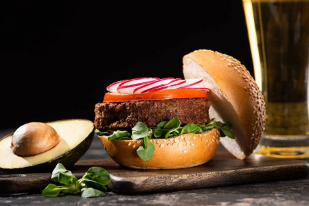 Photo for Selective focus of tasty vegan burger with vegetables served on wooden cutting board with avocado and beer isolated on black - Royalty Free Image