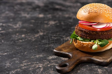 Photo for Tasty vegan burger with vegetables served on wooden cutting board on textured surface - Royalty Free Image