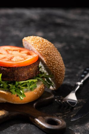 Photo for Tasty vegan burger with tomato and greens served on wooden cutting board with fork on textured surface - Royalty Free Image