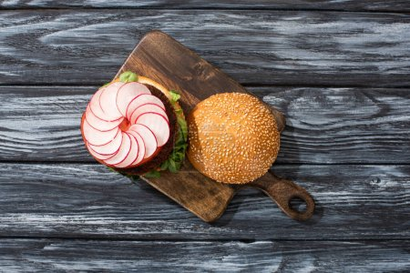 Photo for Top view of tasty vegan burger with microgreens, radish, tomato on cutting board served on wooden table - Royalty Free Image