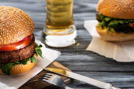Photo for Selective focus of tasty vegan burgers served on wooden table with beer and cutlery - Royalty Free Image