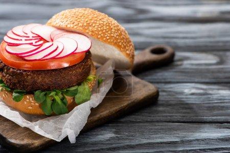 Photo pour Burger végétalien savoureux servi sur planche à découper sur table en bois - image libre de droit