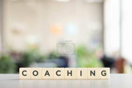 Photo pour Cubes blancs avec inscription de coaching sur le bureau blanc - image libre de droit