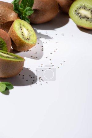selektiver Fokus von Kiwi-Früchten in der Nähe schwarzer Samen auf weißen