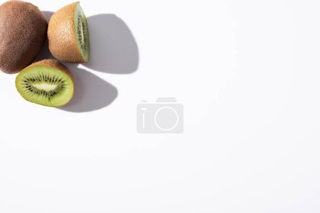 Photo pour Vue de dessus de kiwis entiers près de moitiés sur blanc avec espace de copie - image libre de droit
