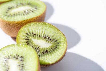 Photo pour Foyer sélectif des moitiés de kiwis verts sur blanc - image libre de droit