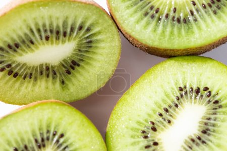 Photo for Top view of green and ripe kiwifruit halves on white - Royalty Free Image