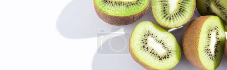 Photo for Panoramic crop of fresh and ripe kiwifruit halves on white - Royalty Free Image
