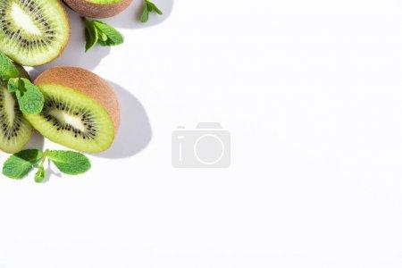 Foto de Vista superior de las mitades maduras de kiwi cerca de la menta sobre blanco - Imagen libre de derechos