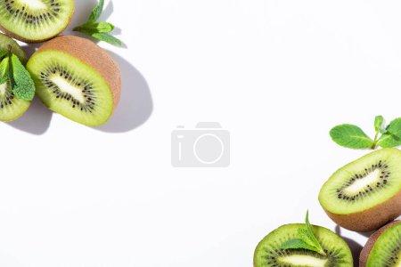 top view of ripe kiwi fruit halves near green peppermint on white
