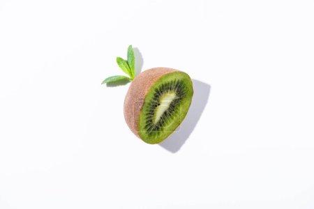 Photo pour Vue de dessus du kiwi bio moitié fruits près de feuilles de menthe poivrée sur blanc - image libre de droit