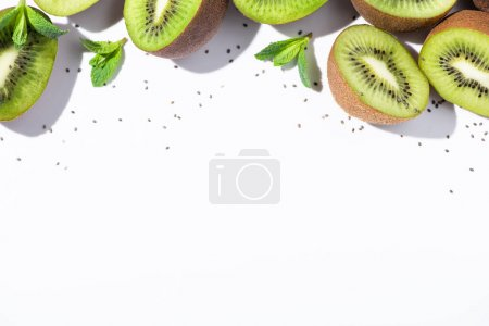 Photo for Top view of organic kiwi fruit halves near green peppermint and black seeds on white - Royalty Free Image