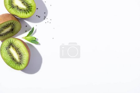 Photo for Top view of kiwi fruit halves near green peppermint and black seeds on white - Royalty Free Image