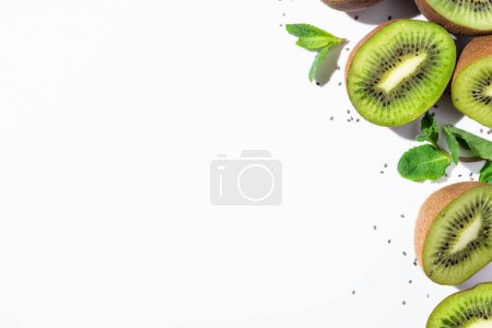 Photo for Top view of tasty kiwi fruit halves near green peppermint and black seeds on white - Royalty Free Image