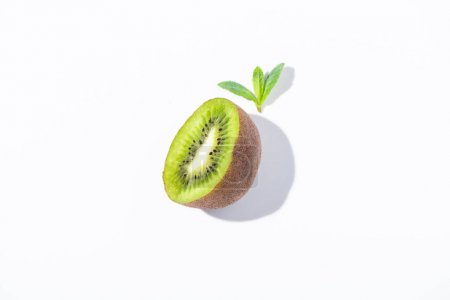 Photo for Top view of fresh kiwi fruit half near peppermint leaves on white - Royalty Free Image