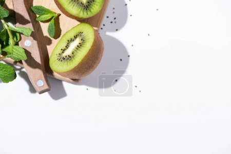 Photo pour Top view of delicious kiwi fruit halves near green peppermint on cutting board on white - image libre de droit