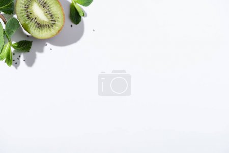 Photo for Top view of green peppermint near fresh kiwi fruit and black seeds on white - Royalty Free Image