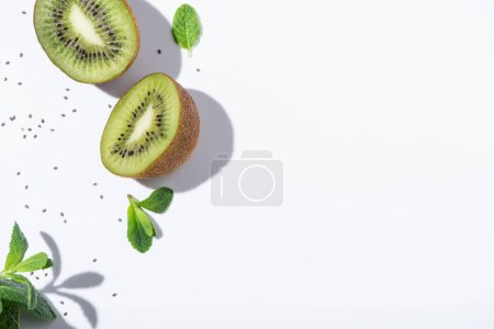 Photo pour Top view of mature kiwi fruits near fresh peppermint and black seeds on white - image libre de droit
