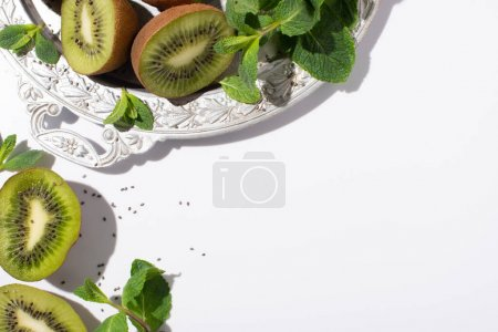 Photo for Top view of green kiwi fruits near fresh peppermint on silver plate on white - Royalty Free Image