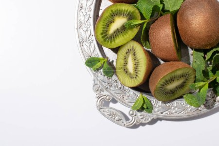 Photo for Top view of tasty kiwi fruits near fresh peppermint on silver plate isolated on white - Royalty Free Image