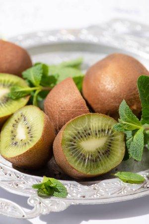 Foto de Enfoque selectivo de frutas kiwi sabrosas cerca de la menta fresca en la placa. - Imagen libre de derechos