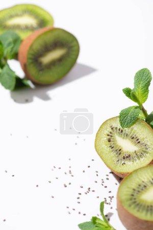 Foto de Enfoque selectivo de sabrosas frutas kiwi cerca de menta fresca y semillas negras en blanco - Imagen libre de derechos