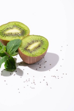 tasty kiwi fruits near fresh peppermint and black seeds on white