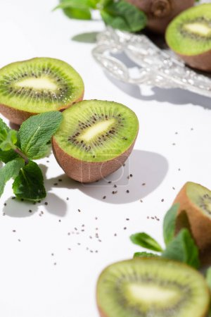 Photo for Selective focus of green kiwi fruits near peppermint and black seeds on white - Royalty Free Image