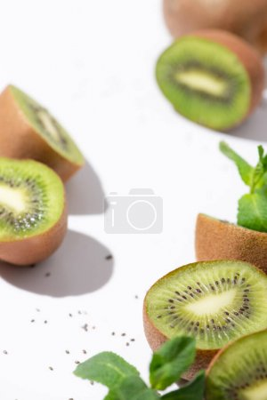 Photo for Selective focus of kiwi fruits near organic peppermint and black seeds on white - Royalty Free Image