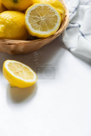 Photo for Close up view of basket of fresh lemons and napkin on white background - Royalty Free Image