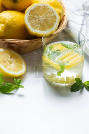 close up view of fresh ginger lemonade in glass near basket of lemons and mint on white background