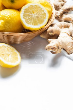 close up view of basket of fresh lemons and ginger root on napkin on white background