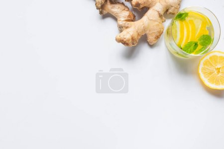 Photo for Top view of fresh lemonade in glass near lemon and ginger root on white background - Royalty Free Image