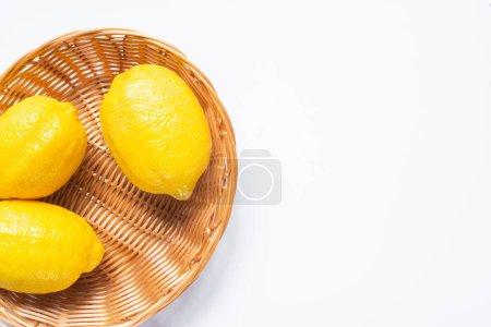 Photo pour Vue de dessus des citrons mûrs dans le panier en osier sur fond blanc - image libre de droit
