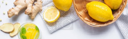 Photo for Top view of fresh lemonade in glass near basket of lemons and ginger root on white background with napkin, horizontal image - Royalty Free Image