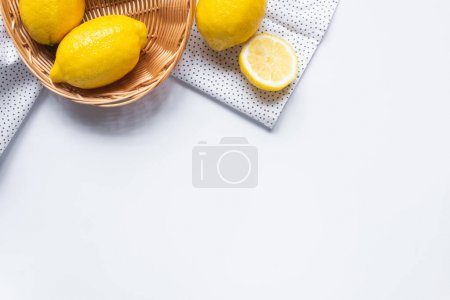 Photo for Top view of ripe lemons in wicker basket on white background with dotted napkin - Royalty Free Image