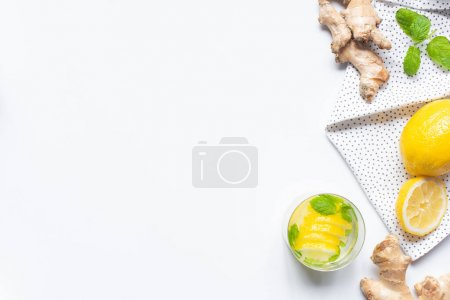 Photo for Top view of fresh lemonade in glass near lemons and ginger root on white background with napkin - Royalty Free Image