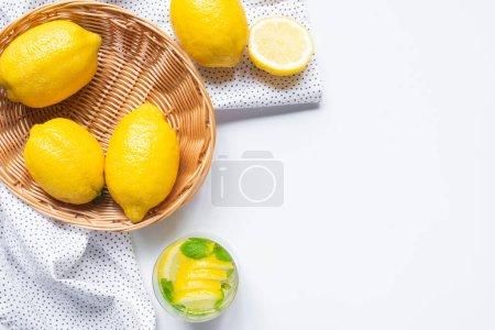 Photo pour Vue de dessus de la limonade fraîche en verre près du panier de citrons sur fond blanc avec serviette - image libre de droit