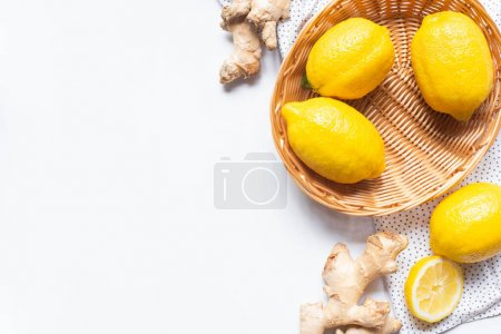 Photo for Top view of ripe lemons in wicker basket on white background with dotted napkin and ginger root - Royalty Free Image