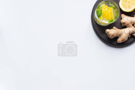 Photo for Top view of fresh lemonade in glass near lemons and ginger root on black board on white background - Royalty Free Image