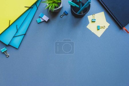 Photo for Top view of paper folders, plant and stationery on blue surface - Royalty Free Image