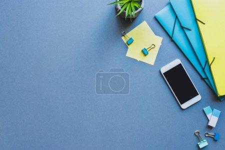 Photo pour Vue du dessus du smartphone près de la papeterie et de la plante sur la surface bleue - image libre de droit