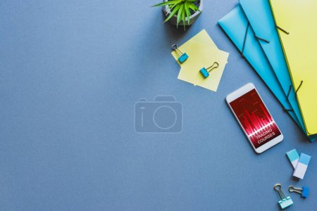 Photo for Top view of stationery and smartphone with trading courses app on blue surface - Royalty Free Image