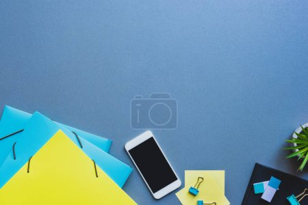 Photo for Top view of smartphone with blank screen near paper folders and stationery on blue background - Royalty Free Image