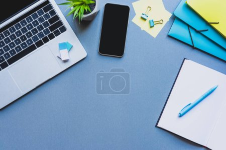 Photo for Top view of smartphone, laptop and stationery on blue background - Royalty Free Image