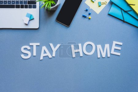 Photo for Top view of lettering stay home near smartphone, laptop and stationery on blue surface - Royalty Free Image