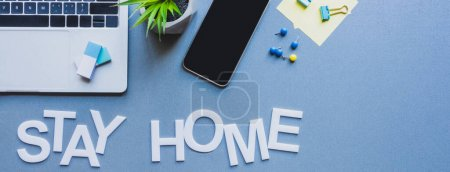 Photo for Panoramic crop of gadgets, stationery and plant near stay home lettering on blue surface - Royalty Free Image