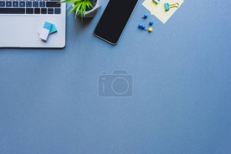 Photo for Top view of laptop, smartphone with blank screen and stationery on blue background - Royalty Free Image