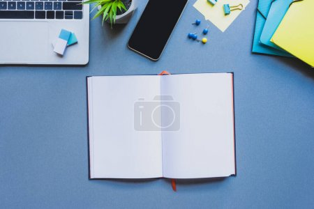Photo for Top view of open notebook near digital devices and office supplies on blue surface - Royalty Free Image