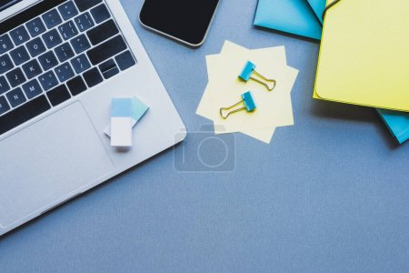 Photo for Top view of gadgets, paper folders and on binder clips on sticky notes on blue background - Royalty Free Image